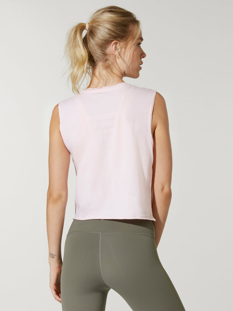 back view of model in light pink cropped muscle tank with small circular logo on chest and green leggings