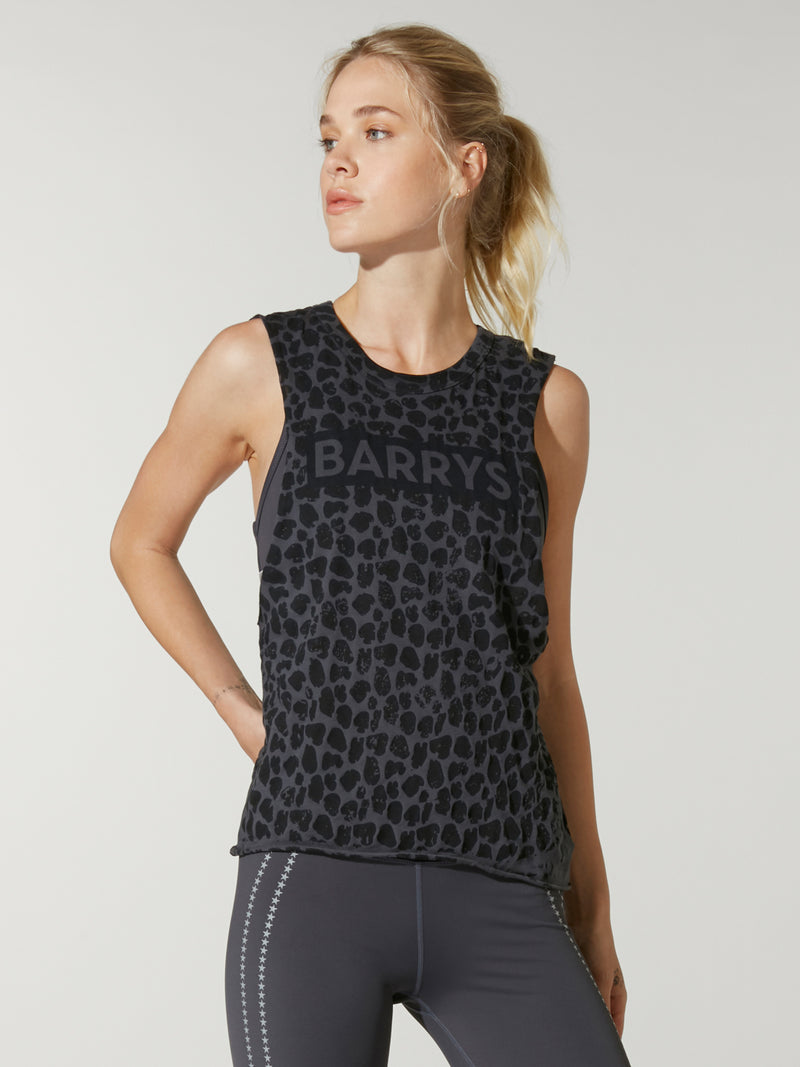 front view model wearing grey and black leopard print tank top with Barry's written on chest and grey leggings