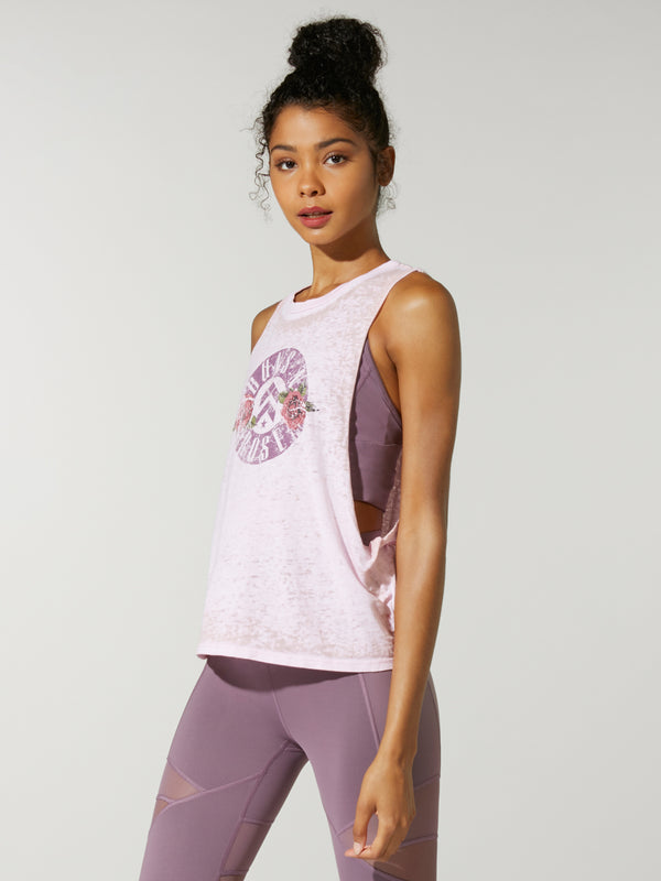 side view of model in light pink muscle tank with guns n roses logo on front and purple leggings