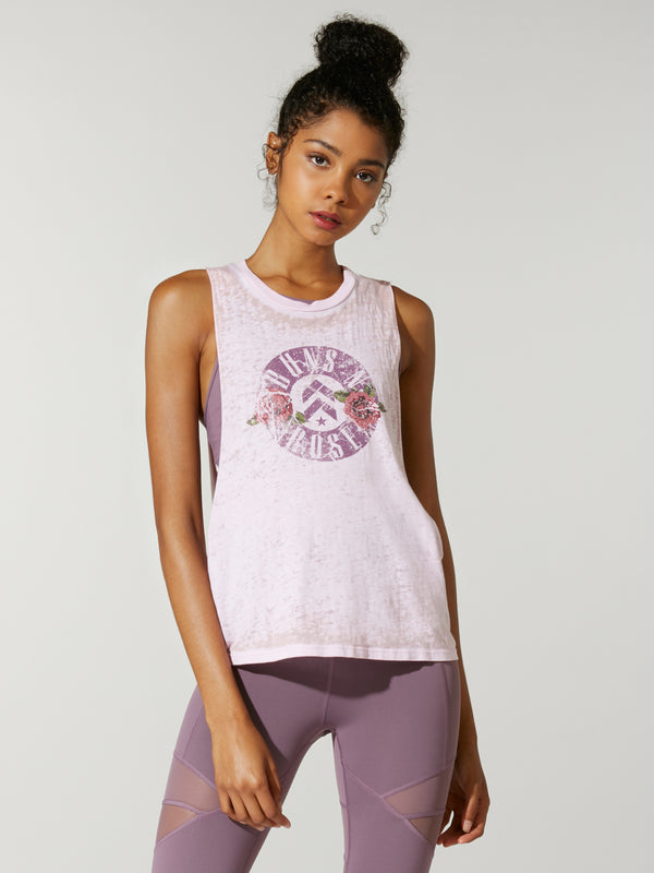 front view of model in light pink muscle tank with guns n roses logo on front and purple leggings