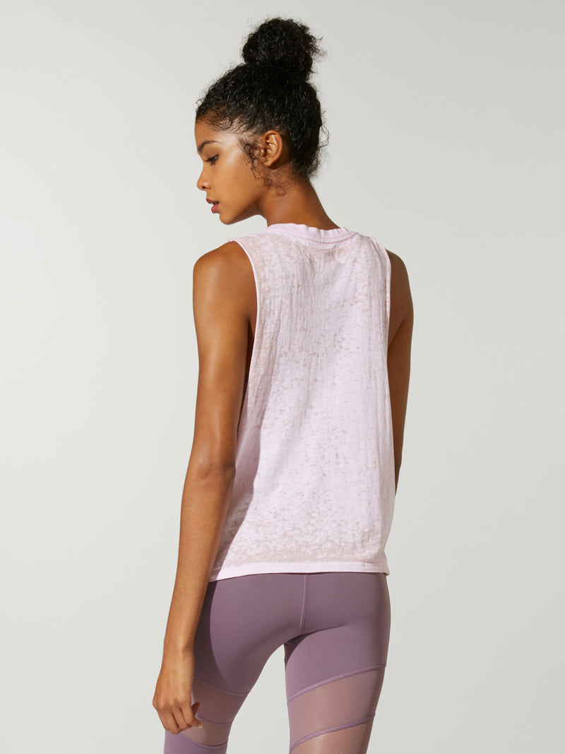 back view of model in light pink muscle tank and purple leggings