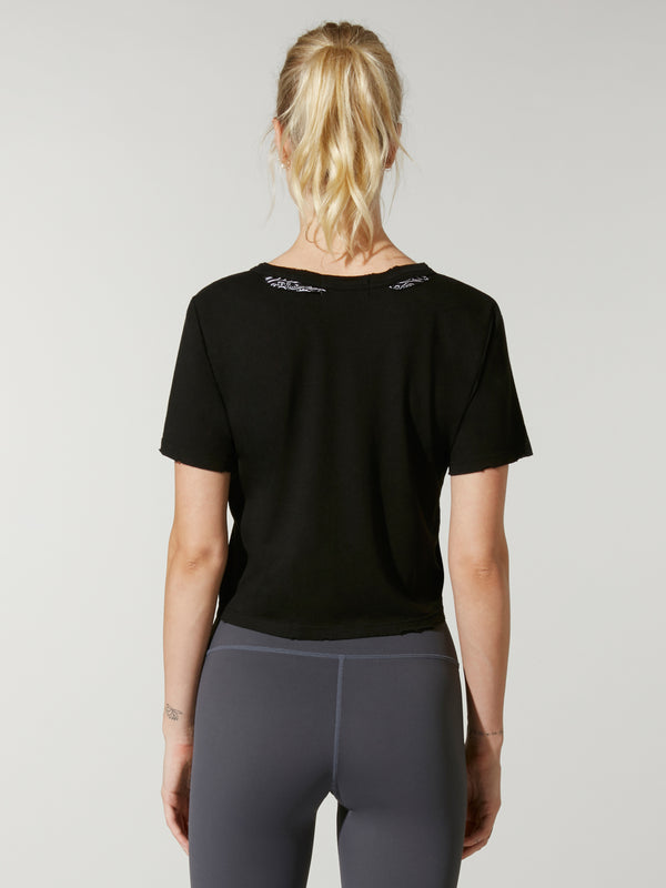 front view of model in black cropped t-shirt with grey Barry's Bootcamp upward arrows and star logo and grey leggings