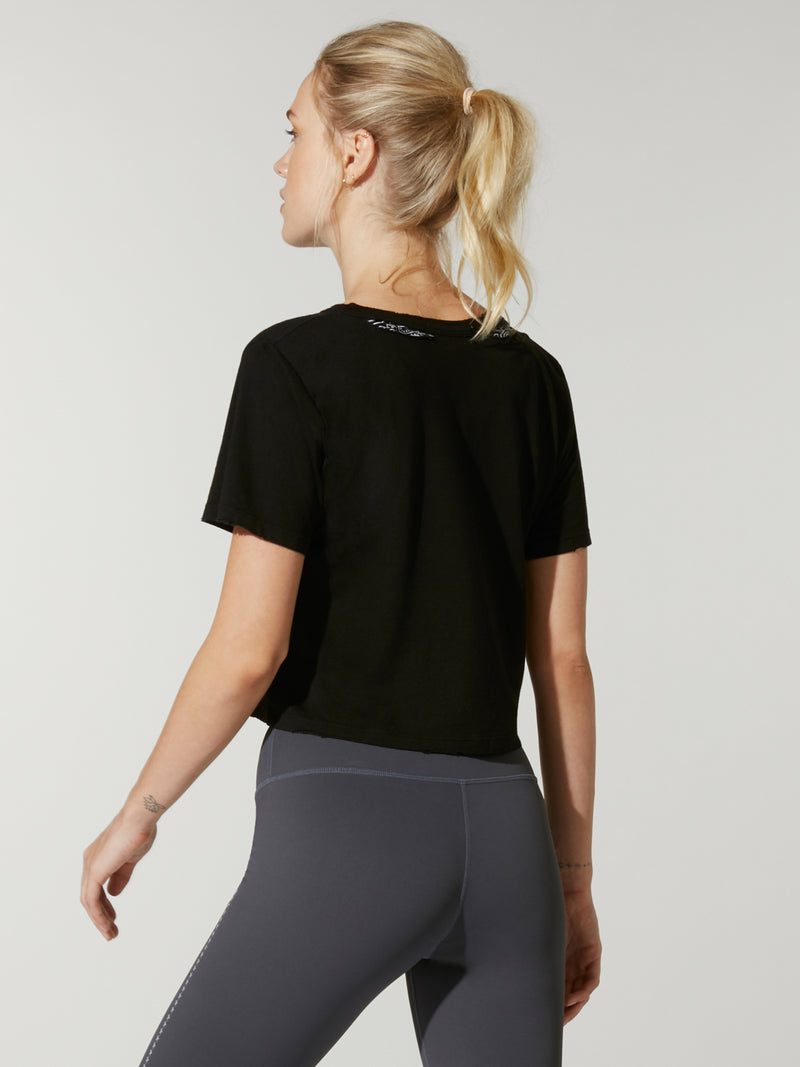side view of model in black cropped t-shirt with grey Barry's Bootcamp upward arrows and star logo and grey leggings
