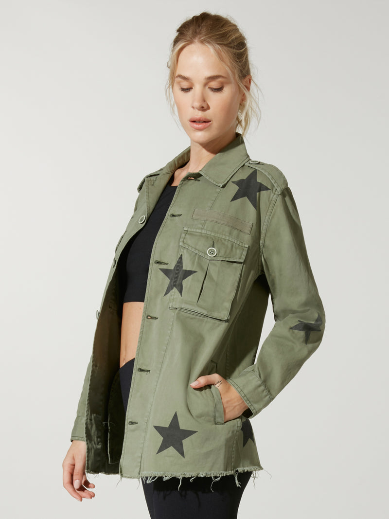 side view of model in black sports bra and leggings under a green army jacket with stars