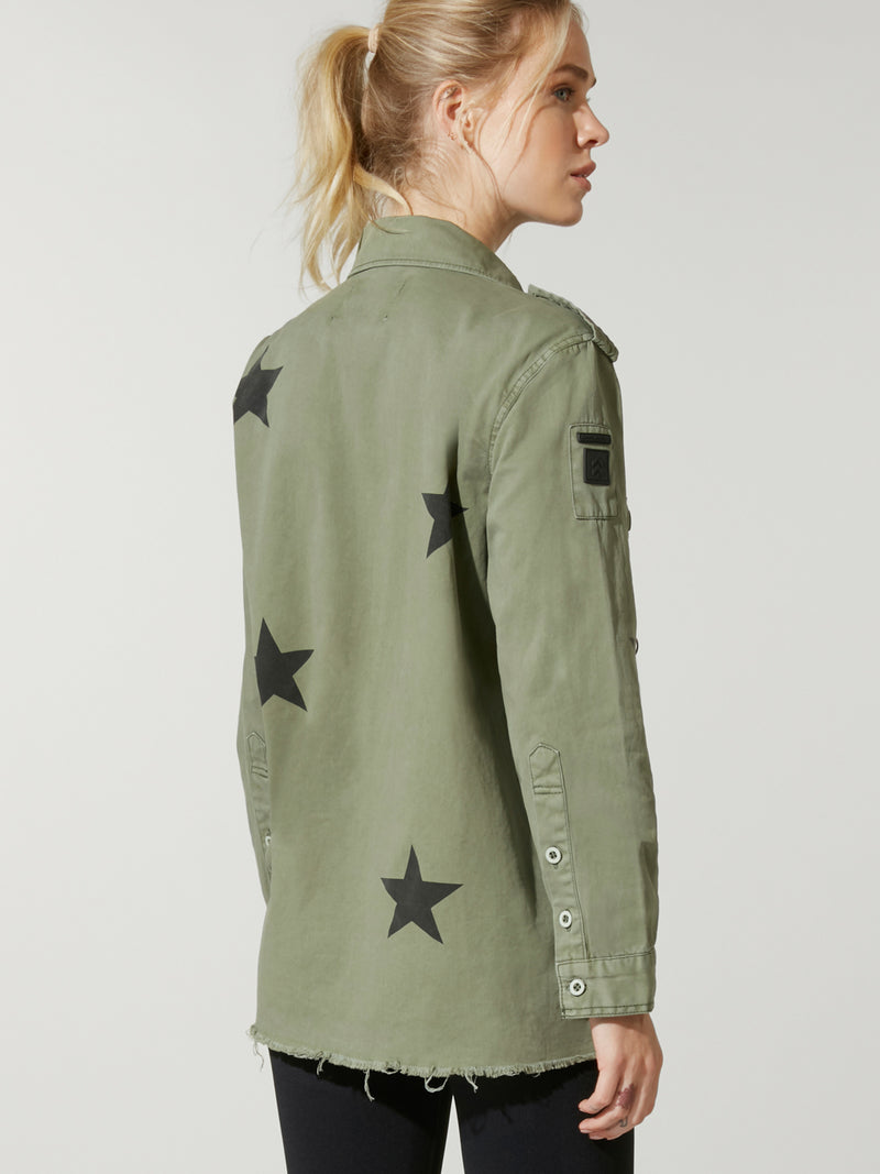 back view of model in black sports bra and leggings under a green army jacket with stars