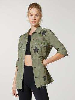 front view of model in black sports bra and leggings under a green army jacket with stars