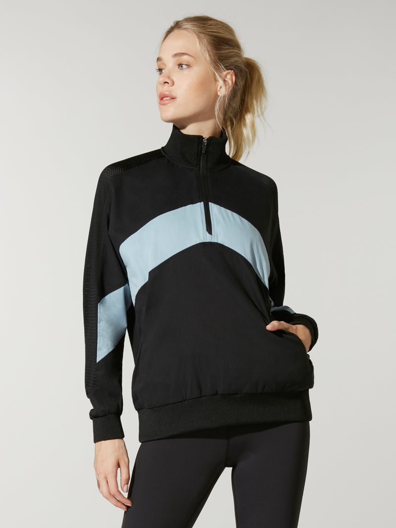 front view of model in black and light blue color blocked pullover with three quarter zip and black leggings