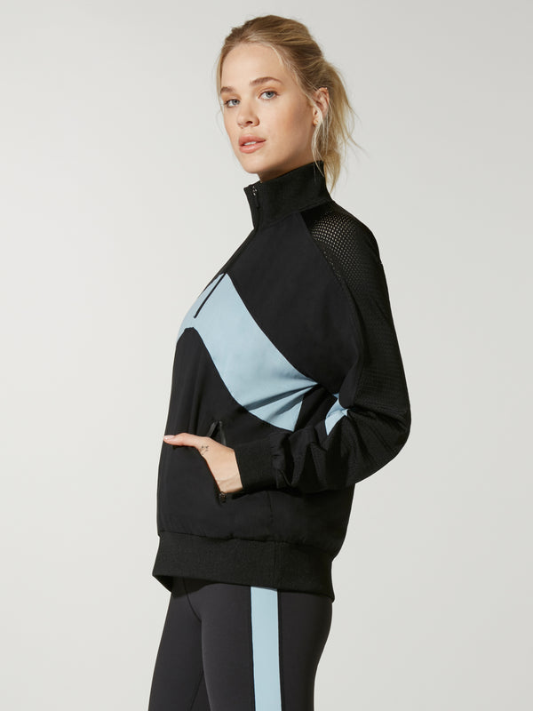 side view of model in black and light blue color blocked pullover with three quarter zip and black leggings