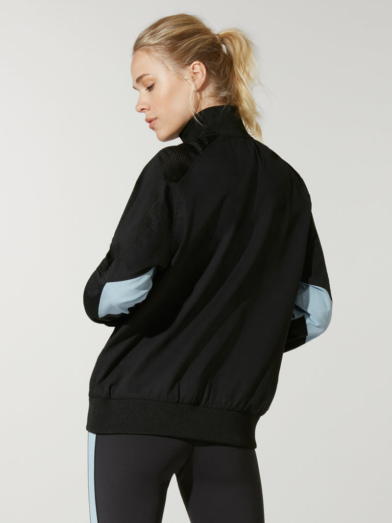 back view of model in black and light blue color blocked pullover with three quarter zip and black leggings