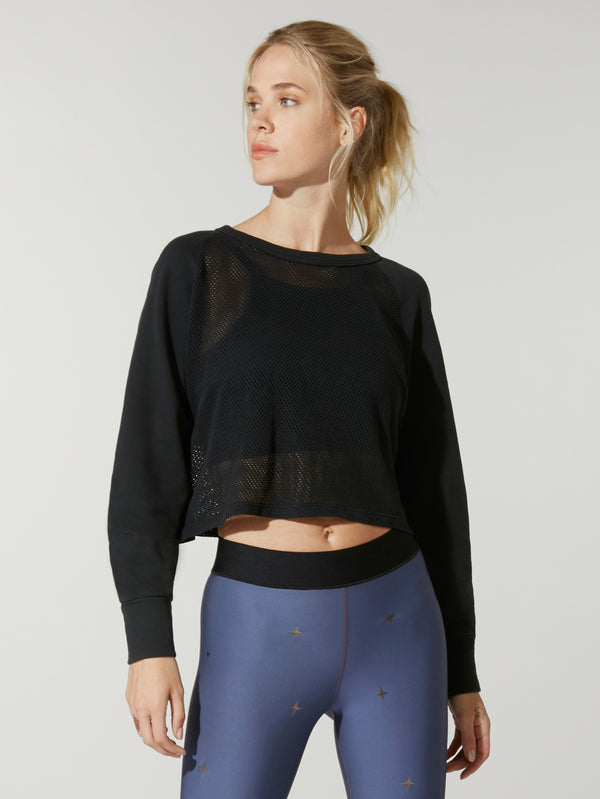 front view of model in black cropped sweatshirt and navy leggings with black elastic waistband