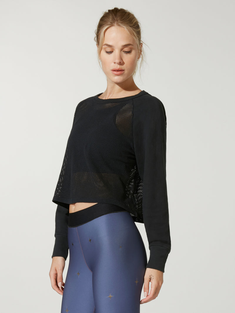 side view of model in black cropped sweatshirt and navy leggings with black elastic waistband