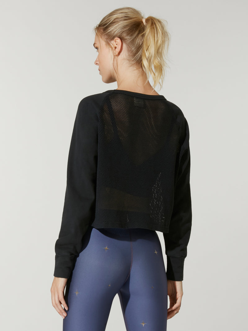 back view of model in black cropped sweatshirt and navy leggings with black elastic waistband