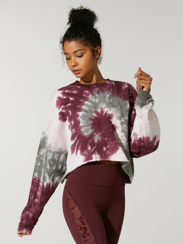 front view of model in cropped purple grey and white tie-dye sweatshirt and dark purple leggings