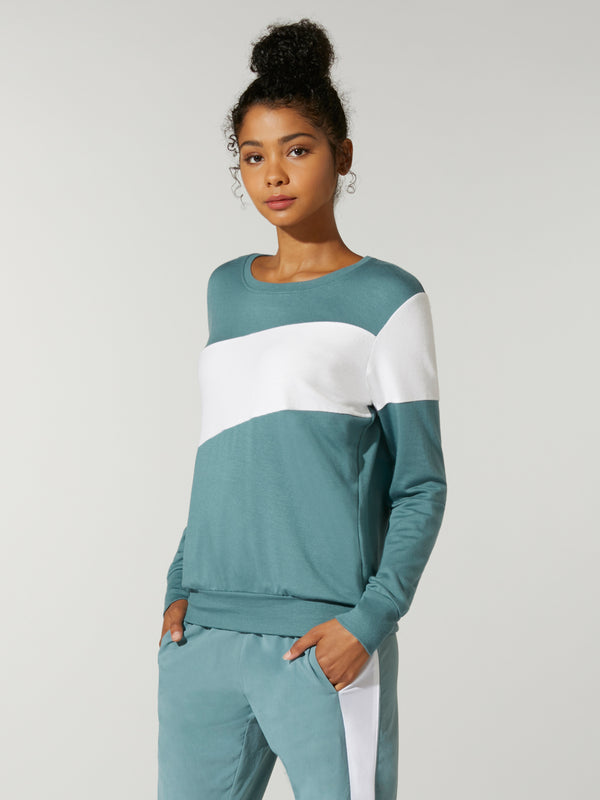 front view of model in teal sweatshirt with white stripe across chest and teal sweatpants