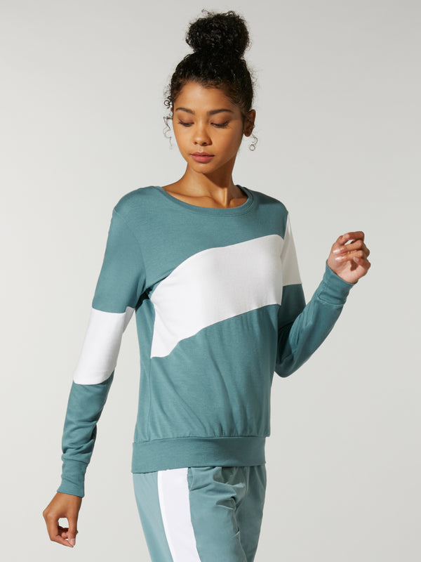 side view of model in teal sweatshirt with white stripe across chest and teal sweatpants