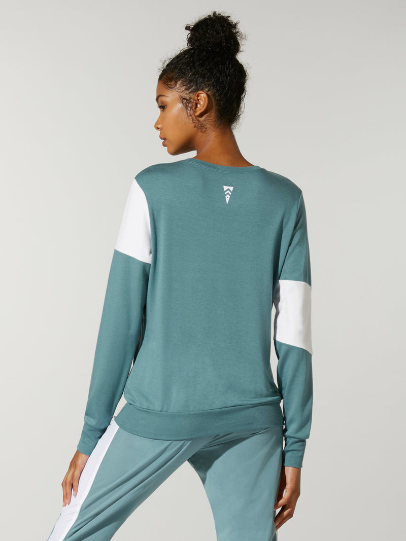 back view of model in teal sweatshirt with white stripe across chest and teal sweatpants