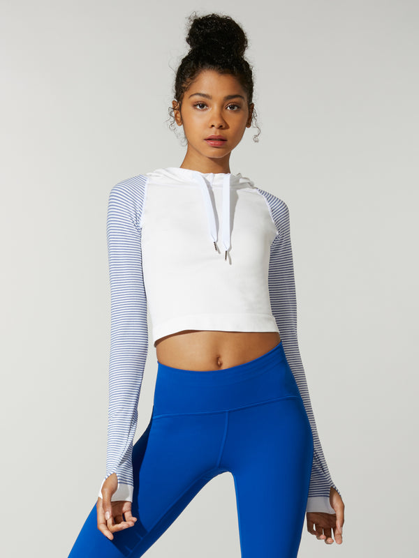 front view of model in white cropped sweatshirt with light blue sleeves and royal blue leggings