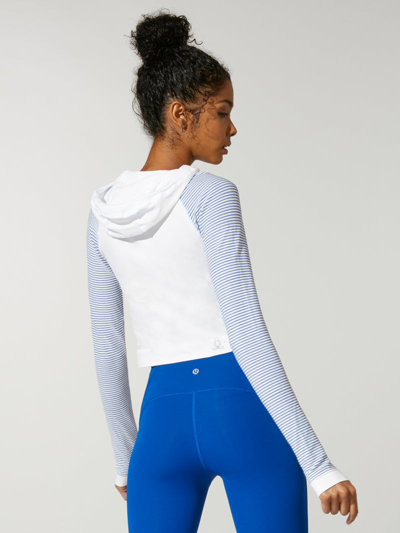 back view of model in white cropped sweatshirt with light blue sleeves and royal blue leggings