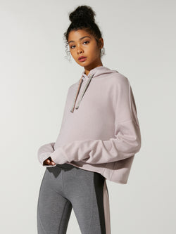 front view of model in thinner blushed colored cropped hoodie and grey leggings