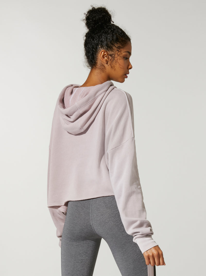 back view of model in thinner blushed colored cropped hoodie and grey leggings