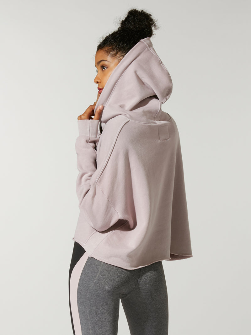 back view of model in thinner blushed colored cropped hoodie with hood up and grey leggings