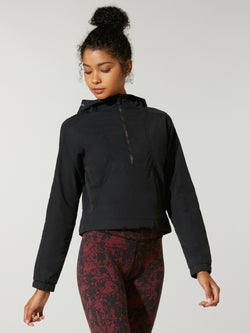 front view of model in black cropped hoody and dark red and black leggings