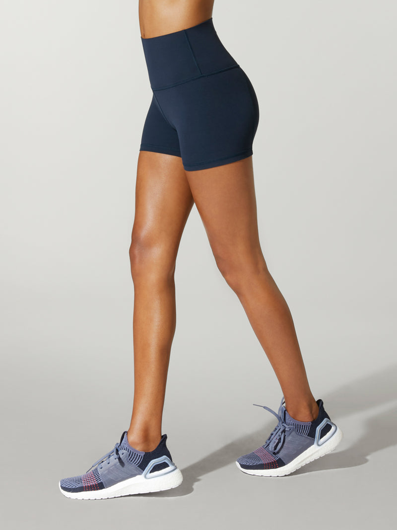 Side view of model wearing navy bike shorts