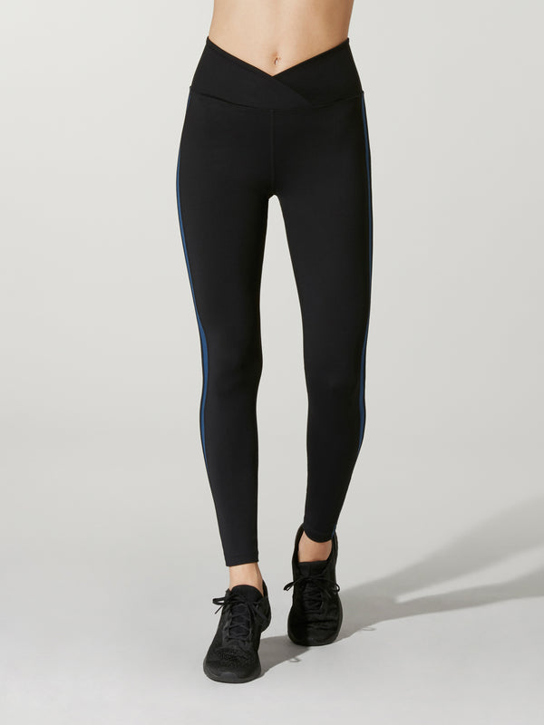 front view of model in black athletic leggings with dipped-front waistband and black sneakers