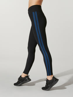 side view of model in black athletic leggings with blue stipe down leg and dipped-front waistband and black sneakers