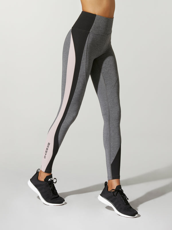 Side view of model wearing gray leggings with black and pink stripes down the side