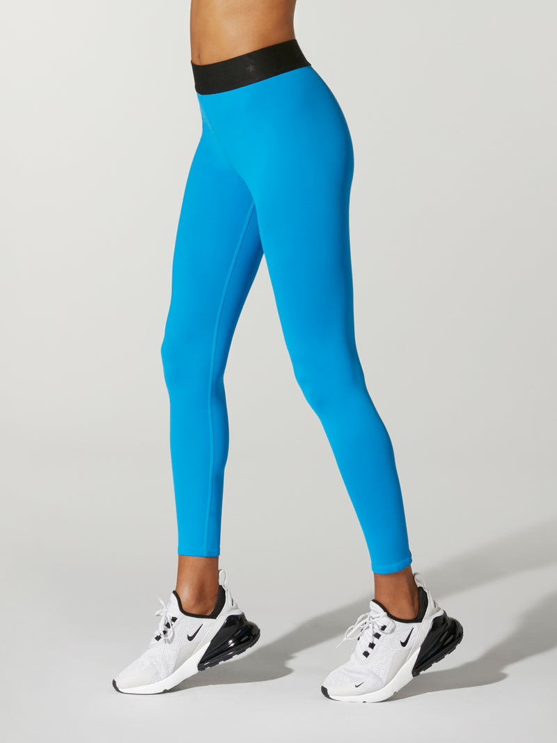 side shot of model wearing bright blue FIT LIGHTNING SPRINTER TIGHT with black waist band