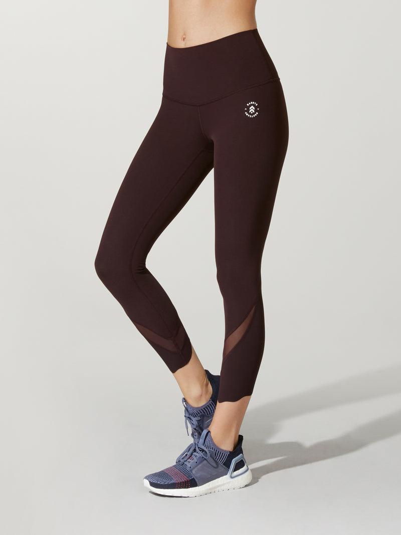 front view of model in dark plum leggings with mesh detail at ankle and purple sneakers