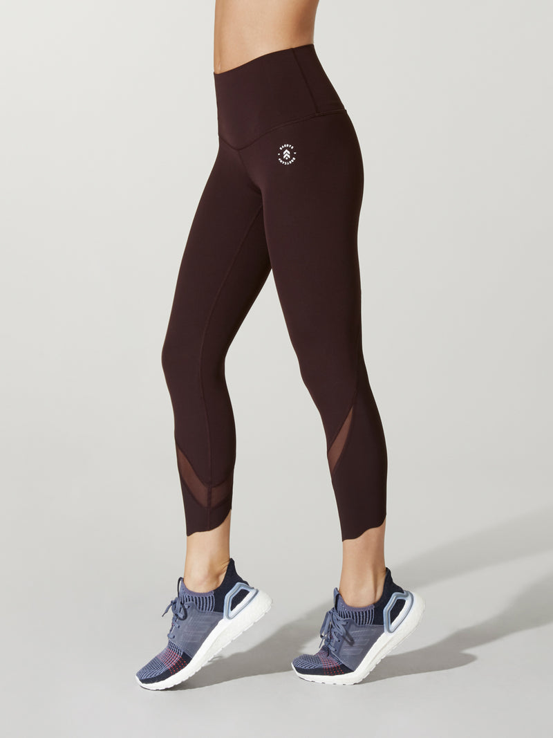 side view of model in dark plum leggings with mesh detail at ankle and purple sneakers