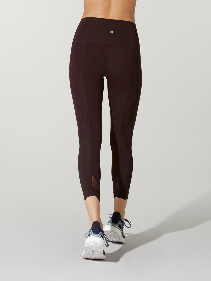 back view of model in dark plum leggings with mesh detail at ankle and purple sneakers