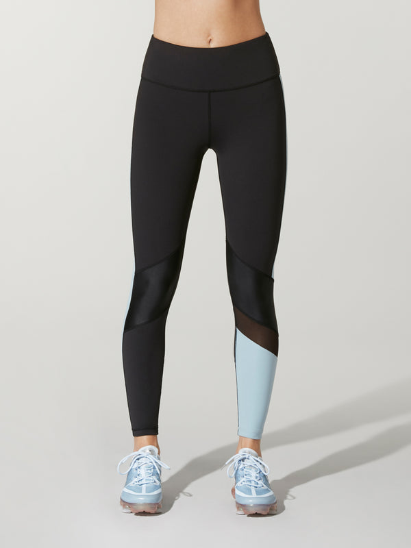front view of black Alala freestyle tights with light blue blocking on one calf