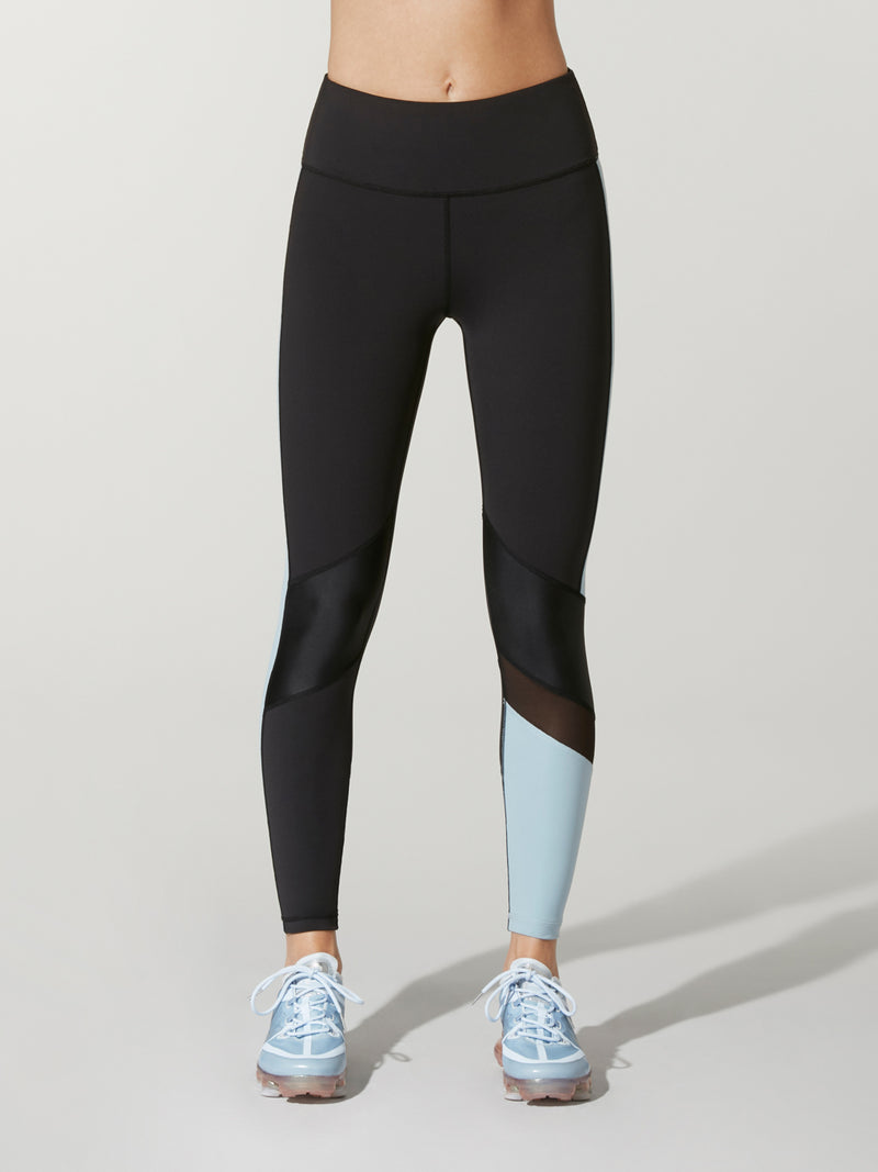 74e9766c5e605 front view of black Alala freestyle tights with light blue blocking on one  calf