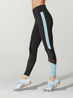 b936cb60f906c side view of black Alala freestyle tights with light blue blocking on one  calf and light