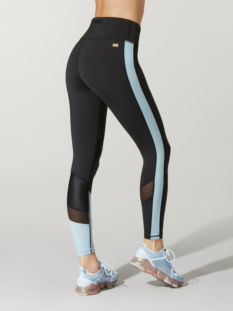 bfa2c7c5132e0 back view of black Alala freestyle tights with light blue blocking on one  calf and light
