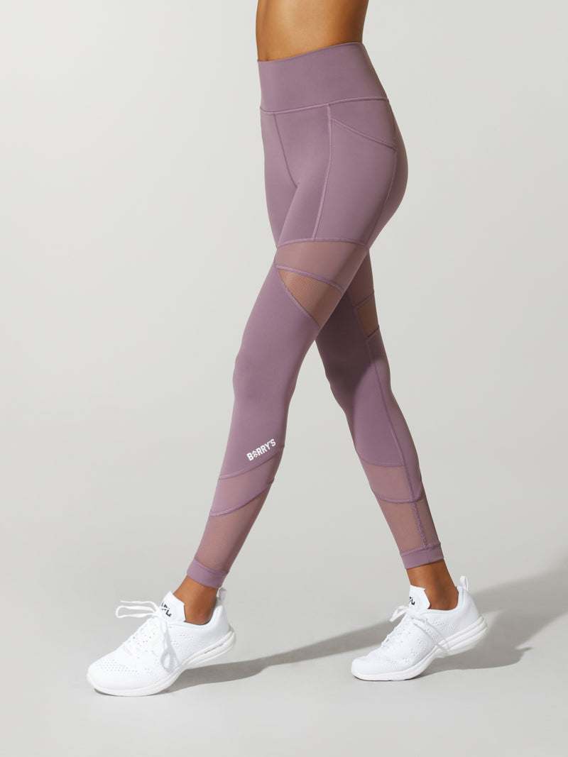side view of model in lavender leggings with mesh details on the thighs and white sneakers