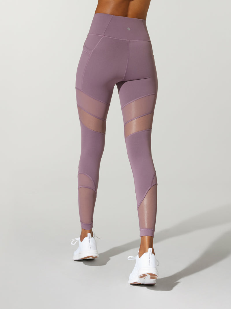 back view of model in lavender leggings with mesh details on the back of thighs and white sneakers