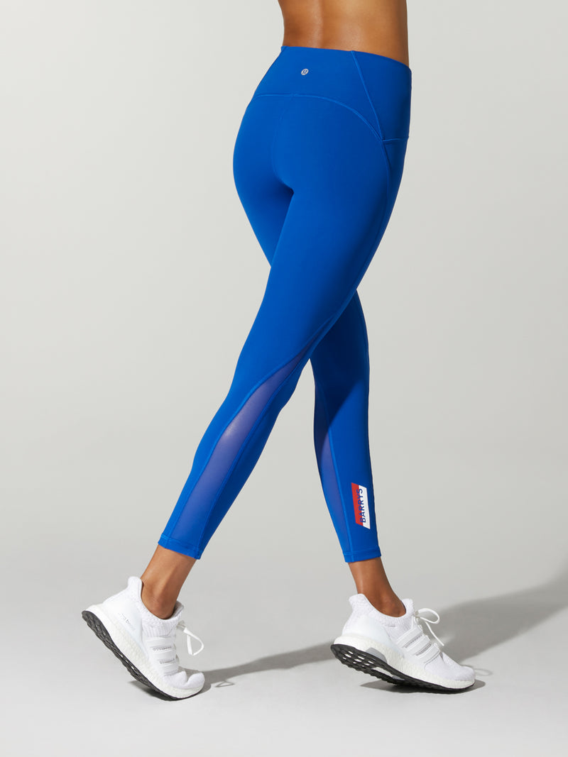 back view of model in royal blue leggings and white sneakers