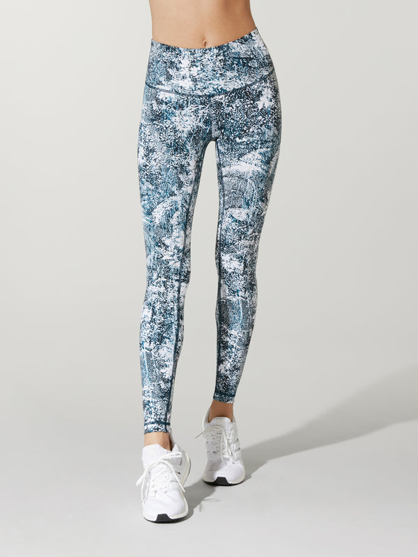 front view of model in light blue and white swirl patterned leggings and white sneakers
