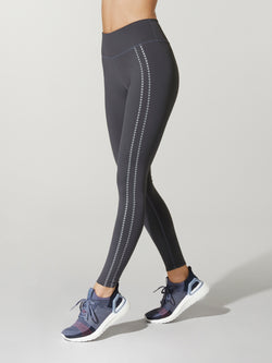 side shot of model wearing dark grey FIT SPEED STORM HIGH WAIST TIGHTs