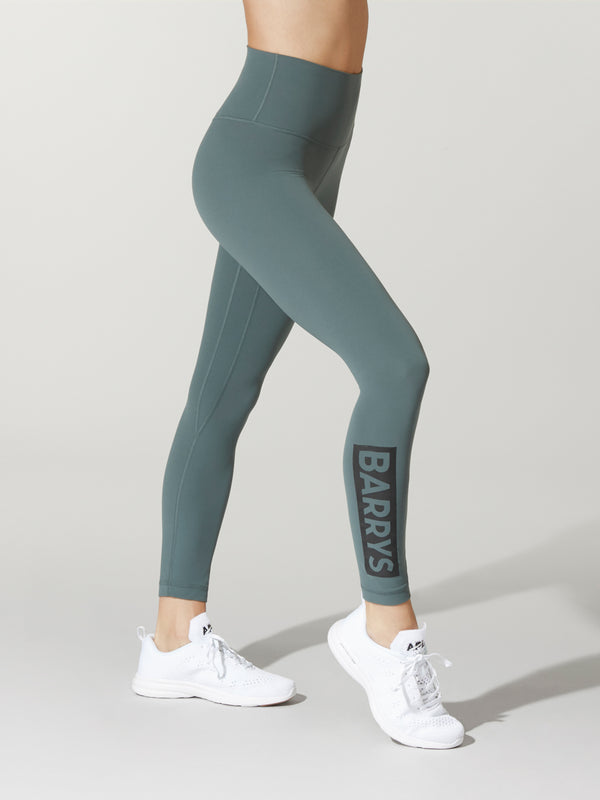 side view of model in teal leggings and white sneakers