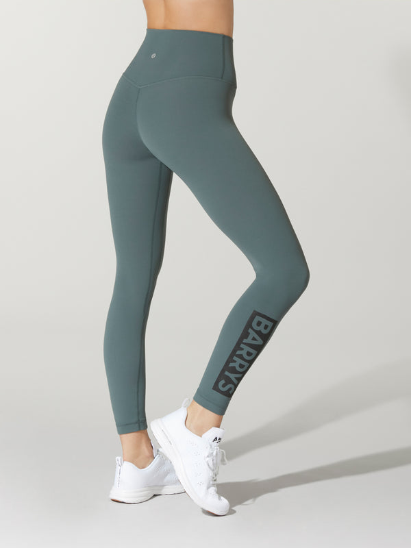 back view of model in teal leggings and white sneakers