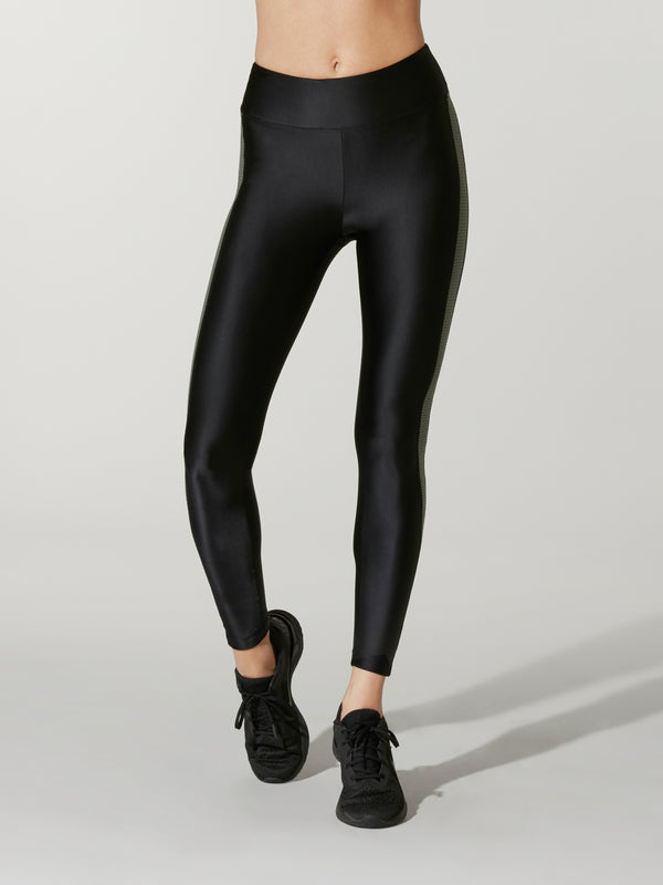 Front view of a model wearing black leggings with black sneakers