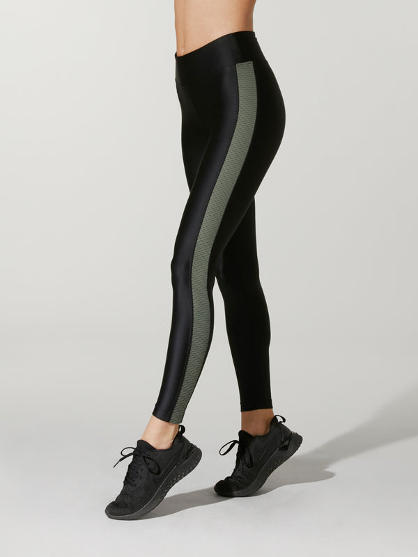 Side view of a model wearing black leggings with a gray side stripe.
