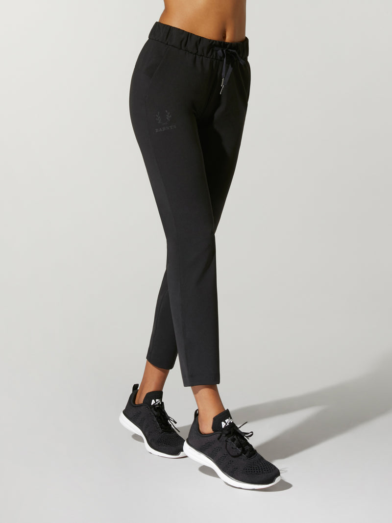 side view of model wearing tight black sweatpants and black sneakers