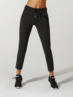front view of model wearing tight black sweatpants and black sneakers