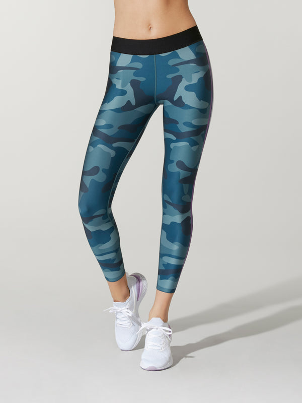front view of model in blue camouflage leggings with black elastic waistband and white sneakers